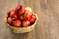 Some peaches in a basket over a wooden surface. Some peaches in a basket over a wooden surface on a green and natural background Stock Photos