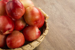 Some peaches in a basket over a wooden surface. Royalty Free Stock Image