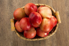 Some peaches in a basket over a wooden surface. Some peaches in a basket over a wooden surface on a green and natural background royalty free stock images