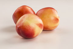 Some peaches in a white background. Fresh fruits Stock Photography
