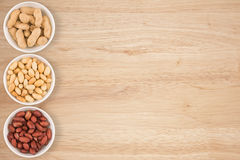 Some peanuts in a cyan bowl on a wooden table. Stock Image