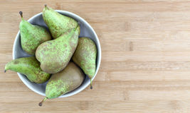 Some pears in a bowl, space fot text. Some pears in a bowl of ceramic, a chopping board as background, space for text on the right, landscape cut Royalty Free Stock Images