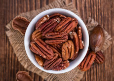 Some Pecan Nuts (selective focus). On wooden background (close-up shot stock image