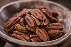 Some Pecan Nuts (selective focus). On wooden background (close-up shot stock photos