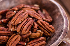 Some Pecan Nuts (selective focus). On wooden background (close-up shot stock photography