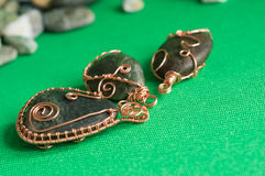 Some pendents of handwork from a stone and a copper wire. On a textile background Stock Image
