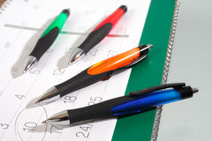 Some pens on a calendar. Studio isolated royalty free stock photography