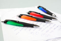 Some pens lie on a paper Stock Photos