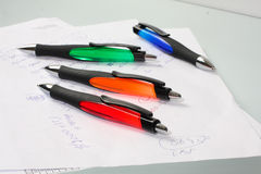 Some pens lie on a paper Stock Images