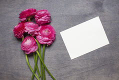 Some peonies on wooden background. With invitation card. Top view Stock Photos