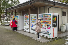 Some people buying some drink with Vending machines. TOYAMA, JAPAN - FEB 13, 2017: Some people buying some drink with Vending machines in front of Toyama castle Stock Image