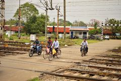 Some people crosses a railway crossing in motorcycle or on cycle near the Tatanagar Rail station royalty free stock photography