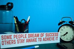 Some people dream of success others stay awake to achieve it Planning on Background of Working Table with Office Supplies. Business Concept Planning on Blue royalty free stock images