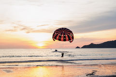 Some people with parachute sport extreme. On beach sunset in twilight and over light the sun stock photos