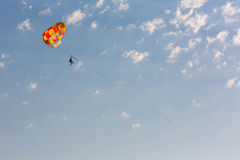 Some people parasailing over the sea. On blue sky background Royalty Free Stock Photo