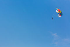 Some people parasailing over the sea. On blue sky background Royalty Free Stock Photography