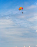 Some people parasailing over the sea. On blue sky background Stock Photos