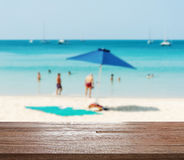 Some people relax on the beach. Wood table top on blurred blue sea with some people relax on the white sand beach - Can be used for display or montage your Stock Photo