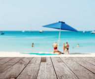 Some people relax on the beach. Wood table top on blurred blue sea with some people relax on the white sand beach - Can be used for display or montage your Royalty Free Stock Image