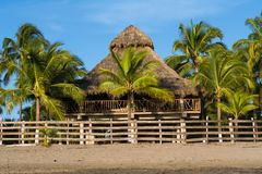Some people rest in the straw and wood house. Landscapes of Boquita beach in Manzanillo Colima Mexico stock photography