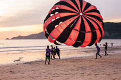 Some people with sport extreme. Phuket Thailand, June 06, 2015: Some people with parachute sport extreme on beach sunset in twilight stock photo