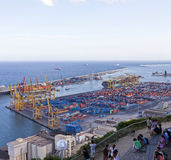 Some people take a rest at the hill Montjuic with a view at the industrial part of the Port of Barcelona Stock Image