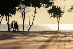 Some people walk on sidewalk near beach. In morning royalty free stock photos
