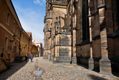 Some people walking through the narrow street of ancient city. PRAGUE: Some people walking through the narrow street of ancient city with narrow cobbled street Stock Image