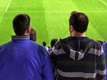 Some people watching a soccer match. Soccer supporters standing and watching a soccer match. Football competition Stock Photo
