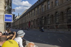 Some people watching and taking pictures of the road on which ri. Ders travel on a background of a beautiful building in the summer sunny day stock photography