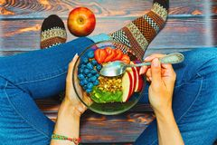 Some person having breakfast on wooden floor. Female person having rural style breakfast of granola, fruits and berries sitting on wooden floor in blue jeans and royalty free stock photo