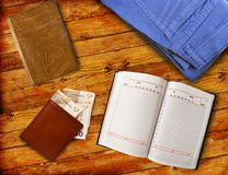 Some personal items on the table. Some personal items on a wooden table. Notebook, purse, book and jeans on the table Stock Photos