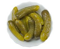 Some pickled cucumbers in a glass bowl on a white. Background Royalty Free Stock Photo