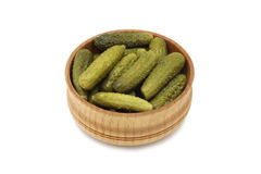 Some pickled cucumbers in a wooden bowl. On a white background Stock Photo