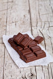Some pieces of chocolate. On rustic wooden background Royalty Free Stock Images