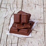 Some pieces of chocolate. On rustic wooden background Royalty Free Stock Photo