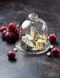 Gorgonzola cheese with nuts ans grapes. Some pieces of delicious gorgonzola cheese on a glass plate with lid Royalty Free Stock Photography