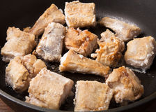 Some pieces of fried fish filet in a frying pan.  Stock Images