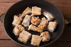 Some pieces of fried fish filet in a frying pan Royalty Free Stock Image