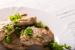 Some pieces of fried meat with parsley greens on a white plate. There is on white boards, a close up, a horizontal shot Stock Photo