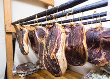 Some pieces of Gailtaler bacon. Pieces of bacon hanging on wooden rods Stock Photography