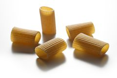 Some pieces of macaroni wholemeal pasta isolated on white backgr. Selective focus on Some pieces of macaroni wholemeal pasta isolated on white background stock image