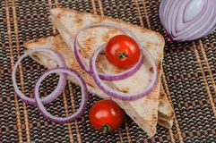 Bread, two tomatoes and onion rings on the table. Some pieces of sandwich. italian tradition food stock photography