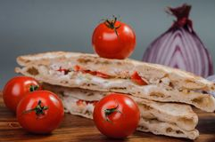 Tasty sandwich and fresh tomatoes. Some pieces of sandwich. italian tradition food stock image