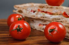 Tasty sandwich and fresh tomatoes. Some pieces of sandwich. italian tradition food royalty free stock images