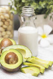Some pieces of sliced avocado on the table and a bottle of milk and maccadamia. Some pieces of sliced avocado on the table and a bottle of milk Stock Photography