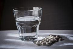 Some pills of different size and color. Along with a water glass Stock Photos