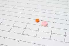 Some pills on electrocardiograms. Records of cardiac activity. Licensed drugs in forms of tablets. Concept of cardiovascular. Some pills on electrocardiograms royalty free stock photo