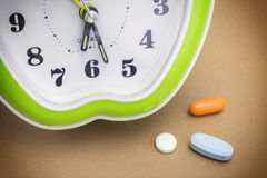 Some pills and green clock. Daily medication treatment Stock Photo