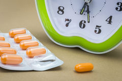 Some pills and green clock. Daily medication treatment Royalty Free Stock Image